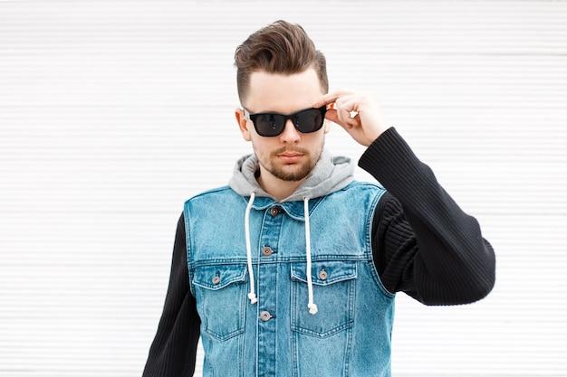 Knappe stijlvolle man met zonnebril in een spijkerjasje in de buurt van een vintage witte houten muur