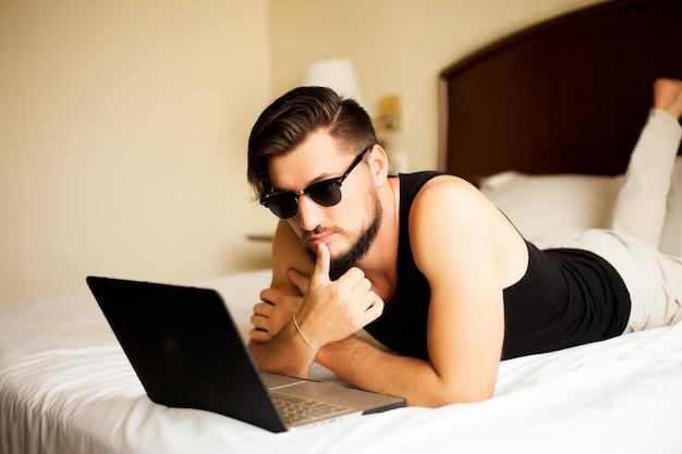 Knappe stijlvolle man poseren buiten in hotel liggend op het bed