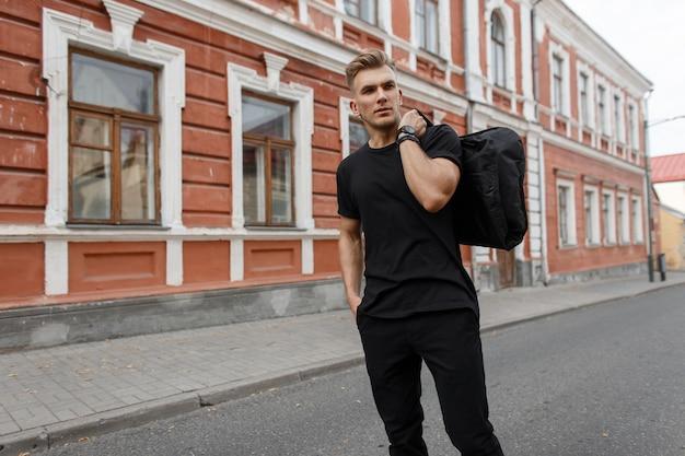 Knappe stijlvolle modieuze jongeman met kapsel in zwart mockup t-shirt met zwarte tas loopt op straat in de stad