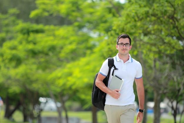 Knappe student die met rugzak en tablet langs bij universiteitspark loopt