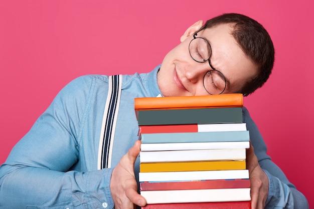 Knappe student draagt blauw shirt, bretels en ronde bril, legt zijn hoofd op stapel boeken en slaapt