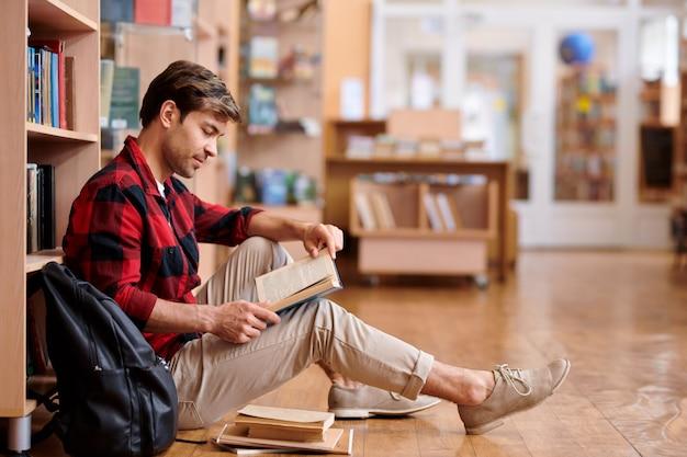 Knappe student in vrijetijdskleding zittend op de vloer van de universiteitsbibliotheek tijdens het lezen van boek of handleiding
