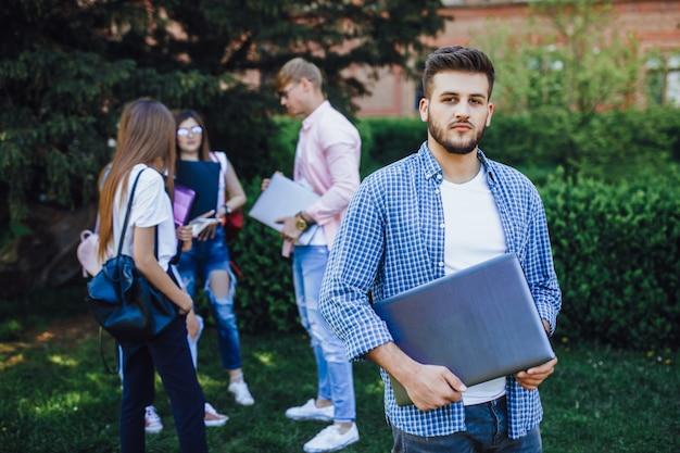 Knappe student man op de campus. houdt een laptop in uw handen. goedendag.