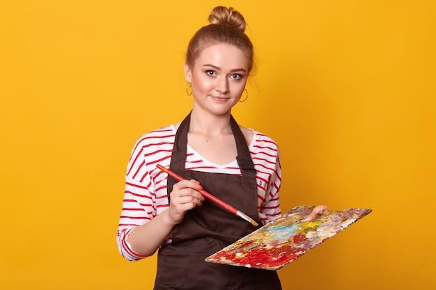 Knappe student met een prettige uitstraling, draagt gestreept overhemd en bruin schort, houdt penseel en kleurenpalet, poseert op geel. creatie en kunstconcept.