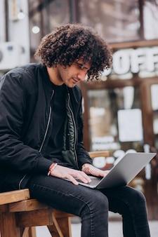 Knappe student met krullend haar die laptop met behulp van