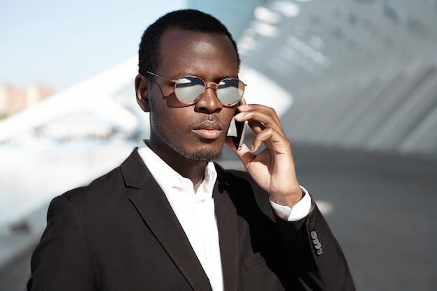 Knappe succesvolle donkere zakenman praten over de telefoon op weg naar kantoor, op zoek peinzend