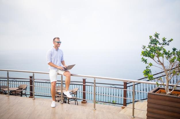Knappe succesvolle jonge mannelijke zakenman die met laptop werkt, kijkt naar de middellandse zee. hij draagt een overhemd en een witte korte broek. werken op afstand op vakantie. vakantie concept