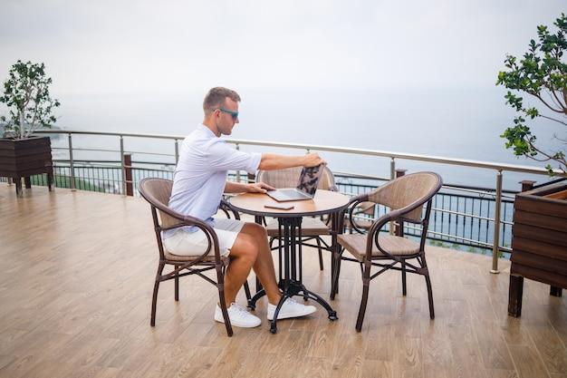 Knappe succesvolle jonge mannelijke zakenman zittend aan een tafel bij het zwembad met een laptop met uitzicht op de middellandse zee. werken op afstand op vakantie. vakantie concept