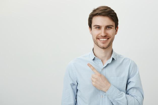 Knappe succesvolle mannelijke ondernemer wijzende vinger linker bovenhoek, glimlachend