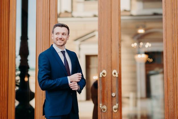 Knappe succesvolle mannelijke uitvoerende werknemer staat in de buurt van deuren van kantoorgebouw