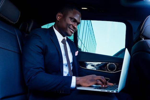 Knappe succesvolle rijke afro-amerikaanse zakenlieden chef in een stijlvol zwart pak en stropdas zittend in een luxe auto en werkt met laptop. concept van geluk en valutamarkt