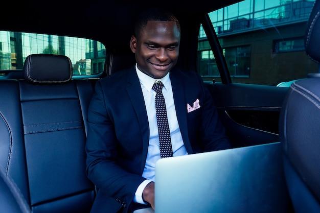 Knappe succesvolle rijke afro-amerikaanse zakenlieden ondernemer in een stijlvol zwart pak en stropdas zittend in een luxe auto en werkt met laptop. concept van geluk en valutamarkt beurs