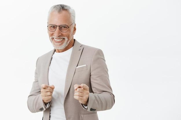 Knappe succesvolle senior man in pak wijzende vingers, brutaal glimlachen