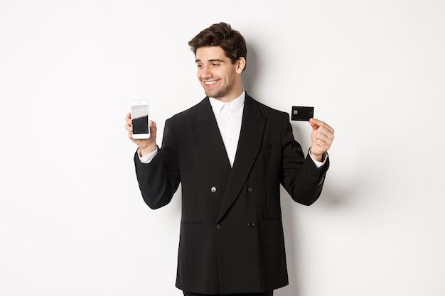Knappe succesvolle zakenman, kijkend naar smartphonescherm en creditcard tonend, staande in zwart pak tegen witte achtergrond