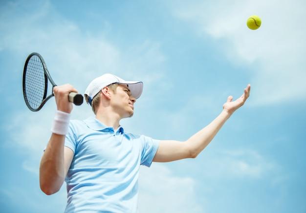 Knappe tennisspeler op hard court die de bal dient.