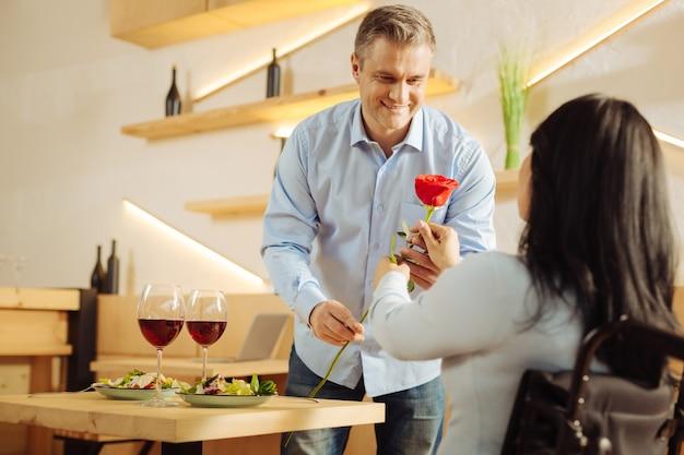 Knappe tevreden blonde man die glimlacht en een rode bloem geeft aan zijn geliefde donkerharige gehandicapte vrouw tijdens een romantisch diner