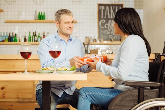 Knappe tevreden blonde man die lacht en een cadeautje geeft aan zijn vrij vrolijke gehandicapte vrouw tijdens het eten