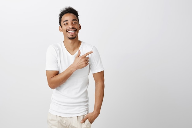 Knappe tevreden donkere man in wit t-shirt wijzend rechterbovenhoek, keuze maken