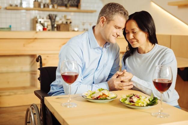 Knappe tevreden gehandicapte man en een aantrekkelijke vrolijke donkerharige vrouw die elkaars hand vasthouden tijdens een romantisch diner