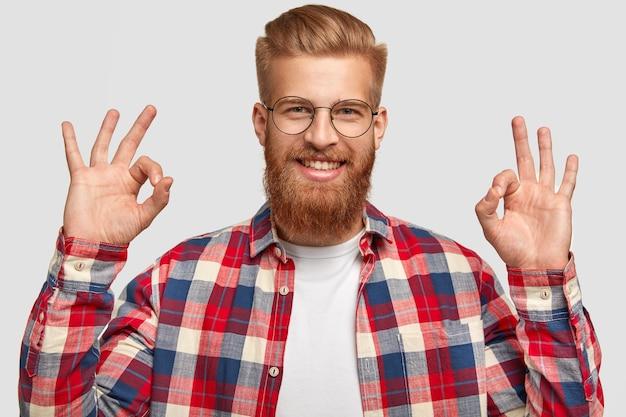 Knappe tevreden gelukkig man houdt van iemands plan, toont goed teken, gebaren in de studio, heeft rode dikke baard en kapsel