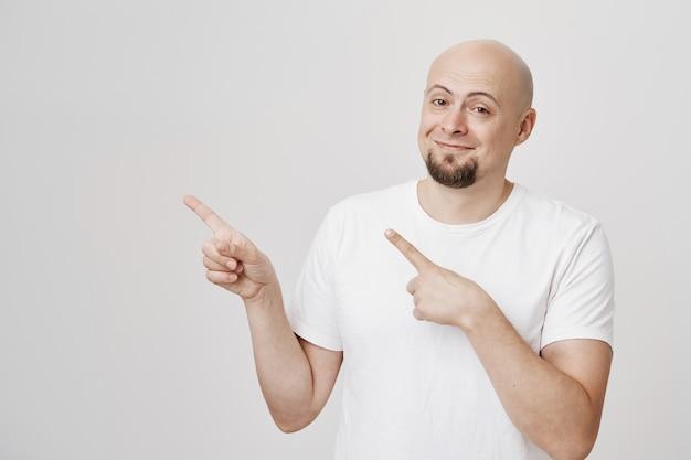 Knappe tevreden man van middelbare leeftijd glimlachend en naar links wijzend