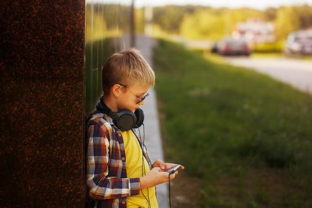 Knappe tiener die aan muziek luistert en telefoon met behulp van