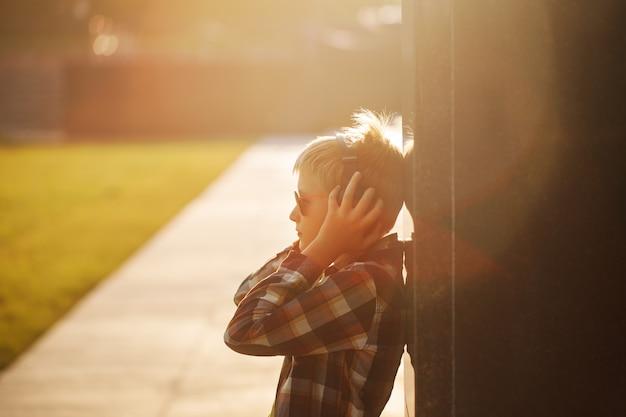 Knappe tiener die aan muziek luistert en telefoon op zonsondergang met behulp van