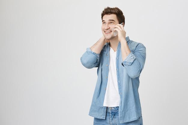 Knappe tienerjongen die aan de telefoon spreekt, zich ongemakkelijk voelt en lacht