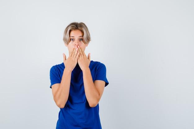 Knappe tienerjongen die de handen op de mond houdt in een blauw t-shirt en er verontrust uitziet. vooraanzicht.