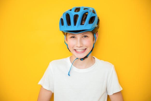 Knappe tienerjongen die de helm van de fietserveiligheid over geïsoleerde gele achtergrond draagt. winnaar concept