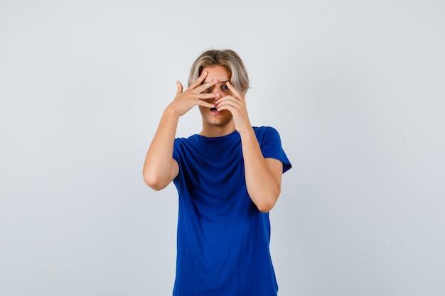 Knappe tienerjongen die door vingers in blauw t-shirt gluurt en er bang uitziet. vooraanzicht.