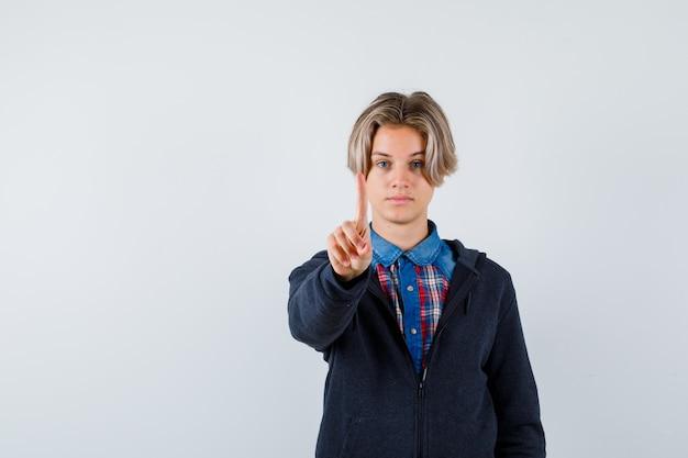Knappe tienerjongen die een klein gebaar in shirt, hoodie laat zien en er zelfverzekerd uitziet, vooraanzicht.