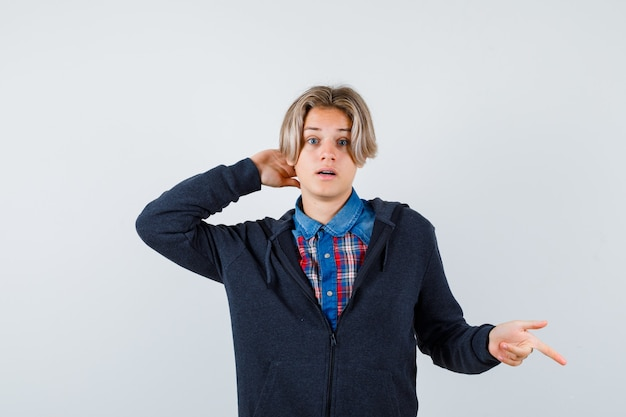 Knappe tienerjongen die naar beneden wijst, met de hand achter het hoofd in shirt, hoodie en verbaasd. vooraanzicht.