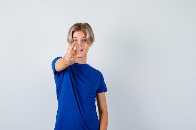 Knappe tienerjongen die naar voren wijst in blauw t-shirt en zich afvraagt, vooraanzicht.