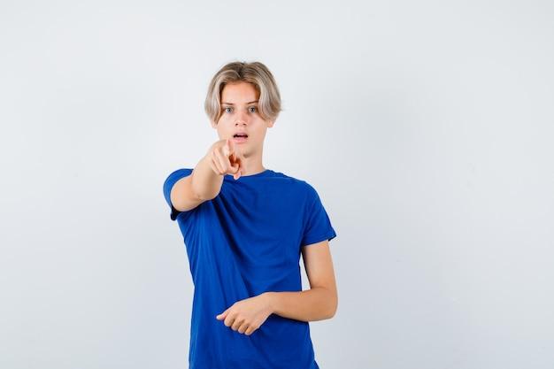 Knappe tienerjongen die naar voren wijst in een blauw t-shirt en er bang uitziet. vooraanzicht.