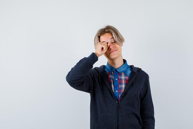 Knappe tienerjongen die oog in overhemd, hoodie wrijft en slaperig kijkt. vooraanzicht.