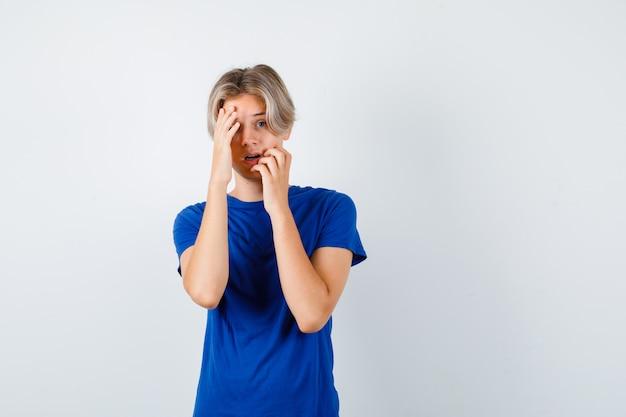 Knappe tienerjongen die zijn handen op zijn gezicht houdt in een blauw t-shirt en er bang uitziet, vooraanzicht.