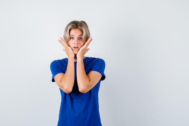 Knappe tienerjongen in blauw t-shirt die de handen op de wangen houdt en er bang uitziet, vooraanzicht.