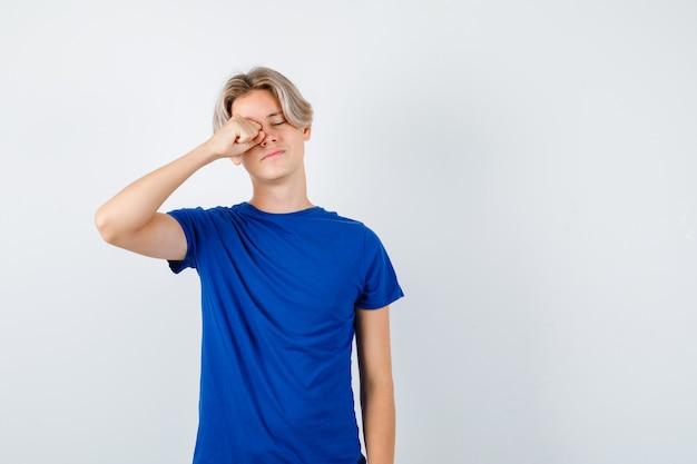 Knappe tienerjongen in blauw t-shirt die in de ogen wrijft en er slaperig uitziet, vooraanzicht.