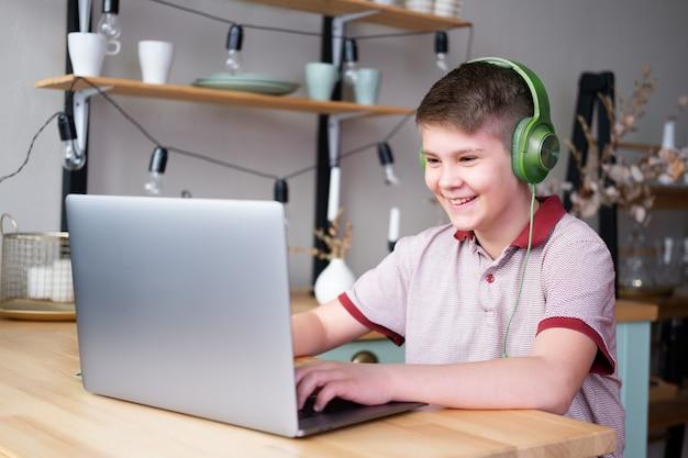 Knappe tienerjongen in koptelefoon online studeren, spelen in videogames met laptop zittend op de keuken.