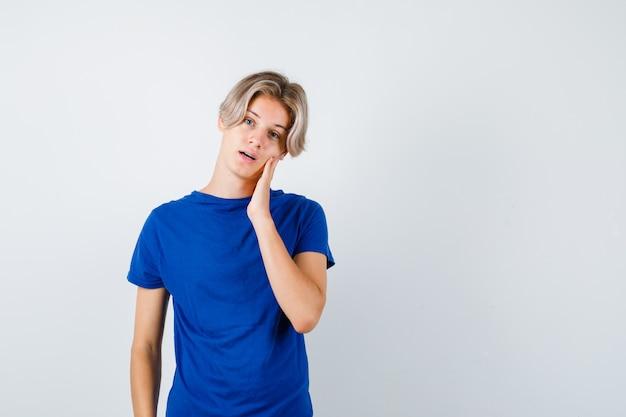 Knappe tienerjongen leunt wang aan de hand in blauw t-shirt en kijkt peinzend, vooraanzicht.