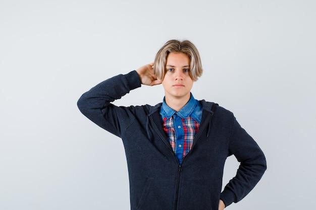 Knappe tienerjongen met hand achter hoofd in overhemd, hoodie en peinzend kijkend. vooraanzicht.