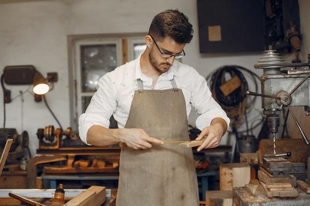 Knappe timmerman die met een hout werkt
