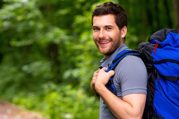 Knappe toerist. knappe jonge man die rugzak draagt en met een glimlach over zijn schouder kijkt terwijl hij in de natuur staat