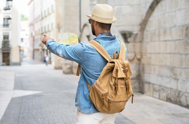 Knappe toeristische man kijkt naar de kaart terwijl hij met de vinger in de richting van het reisconcept van de bestemming wijst...