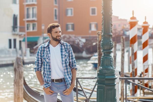Knappe toeristische man staande op de pier tegen prachtig uitzicht op venetiaanse chanal met boten