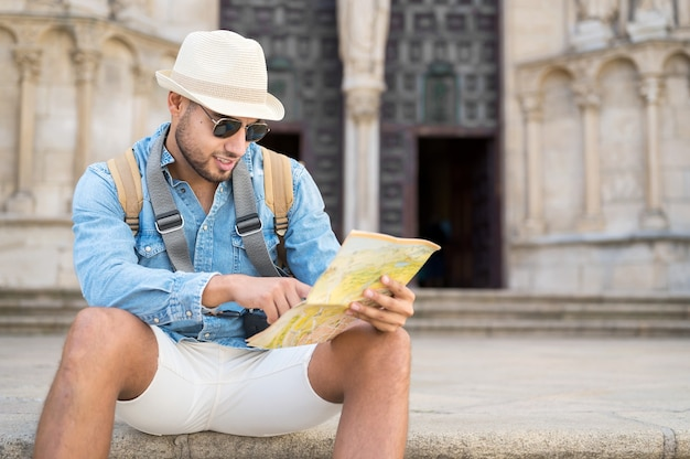Knappe toeristische man wijzend op kaart zoeken in de richting van bestemming reizen concept reis terug...