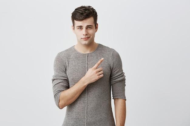 Knappe trendy mens die vrijetijdskleding dragen, bij hoek van zijn mond glimlachen, terloops gekleed, wijzend met wijsvinger opzij op tekst of reclame. mannelijk model poseren.