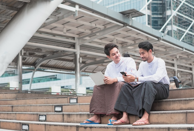 Knappe twee aziatische personen die op trappen zitten met luistermuziek zijn geluk in de stad