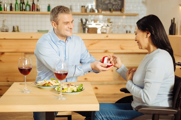 Knappe uitbundige blonde man die lacht en zijn mooie opgetogen gehandicapte vrouw voorstelt terwijl hij een ring vasthoudt en eet